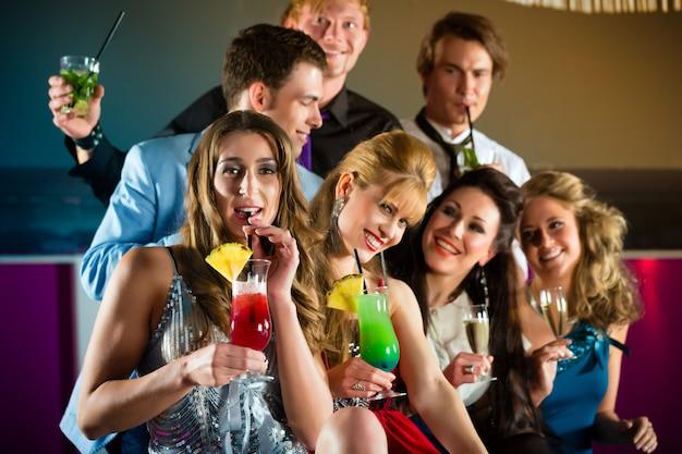 Люди в клубе или баре пьют коктейли