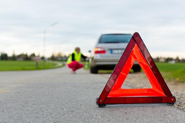 通りに警告の三角形を持つ若い女性