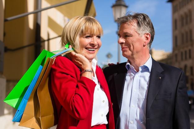 春のショッピングで街を散歩する年配のカップル