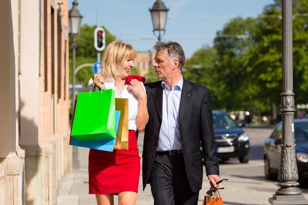 春の街のショッピングを散歩する成熟したカップル