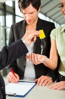 車の販売-女性の自動キーを渡すディーラー