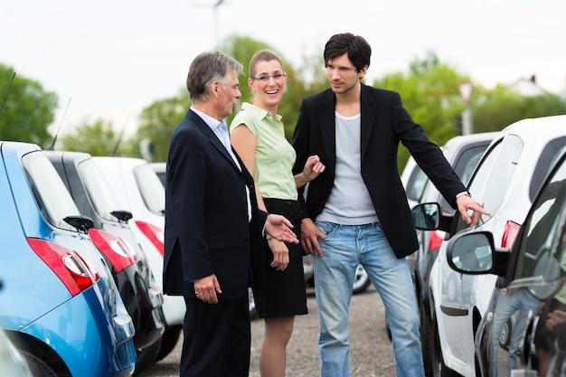 ディーラーの庭で車を探しているカップル