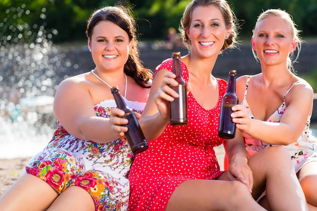 川のビーチでビールを飲む友人