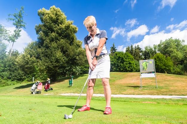 ゴルフ場でティーストロークをしている年配の女性