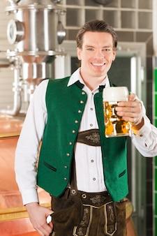 Человек с бокалом пива в пивоварне
