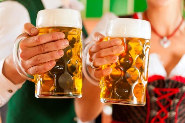 醸造所でビールのグラスを持つ男女