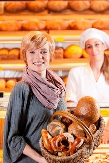 Продавец с покупательницей в пекарне