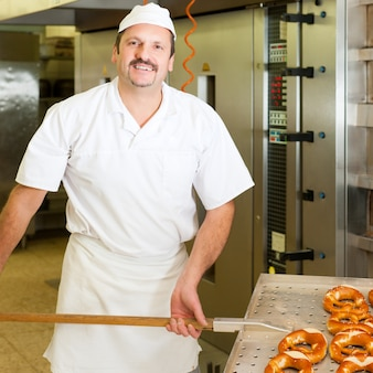 Бейкер в своей пекарне выпекает хлеб