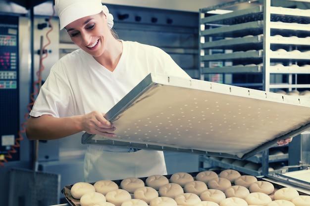 パン屋さんのベーキングでパンのシートを持つベイカー女性