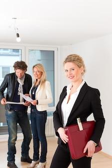 女性の不動産業者と不動産を探している若いカップル