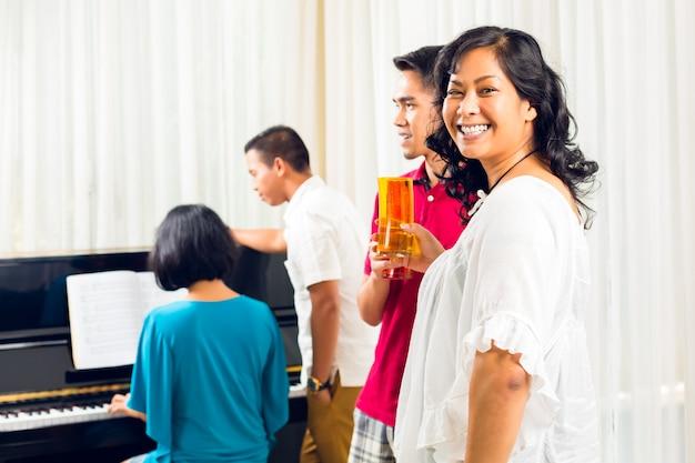 ピアノで一緒に座っているアジアの人々