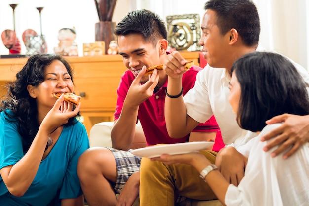 パーティーでピザを食べるアジアの人々