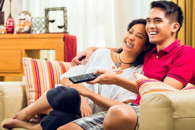 テレビを見ているアジアのカップル