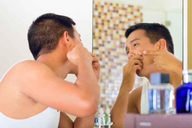 アジア人の顔ににきびを発見