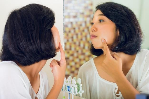 アジアの女性の顔ににきびを発見