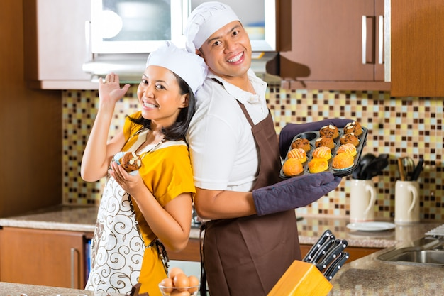 家庭の台所でマフィンを焼くアジアカップル