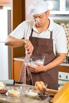 家庭の台所でケーキを焼くアジア人