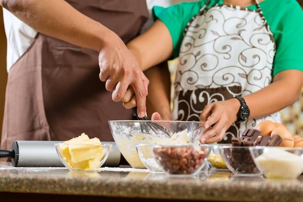 アジアのカップルが家庭の台所でケーキを焼く