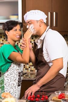 キッチンでチョコレートケーキを焼くアジアカップル