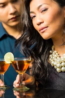 アジアの男と女のバーでカクテル