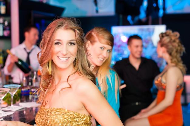 Люди в клубе или баре пьют шампанское