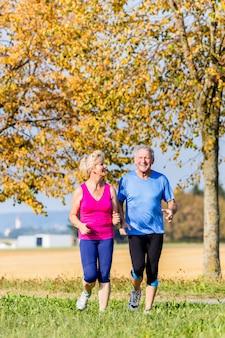 Старший женщина и мужчина работает делать упражнения фитнес