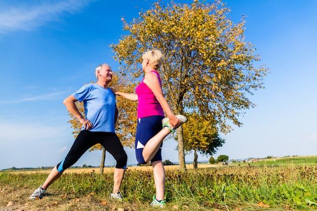 Женщина и мужчина, пожилые люди, занимающиеся спортом на открытом воздухе