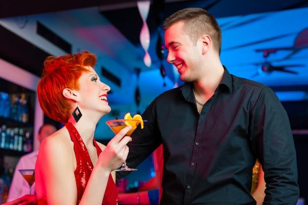 若いカップルのバーやクラブのカクテルを飲む