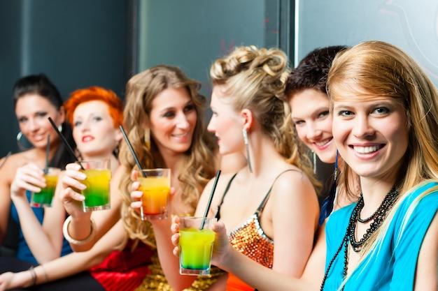 Женщины в клубе или на дискотеке пьют коктейли