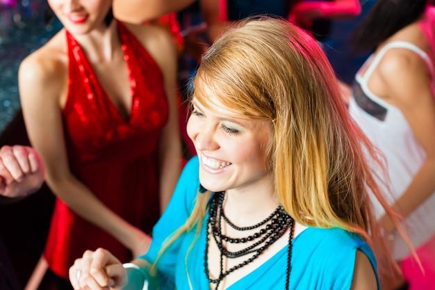 Молодые люди танцуют в клубе или на дискотеке, мужчины и женщины
