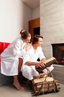 Молодая пара сидит в халате для открытого камина