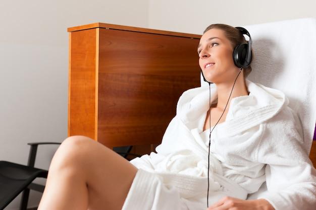 音楽とスパでリラックスした若い女性