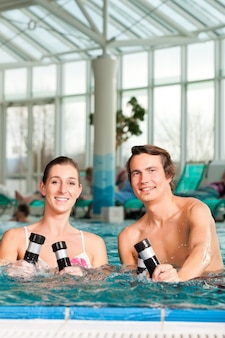フィットネス-スイミングプールの水の下で体操