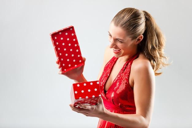 Женщина открывает подарок и рада