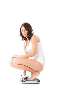 Молодая женщина сидит на корточках в масштабе