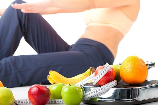 ダイエットとスポーツ-若い女性は腹筋運動をしています