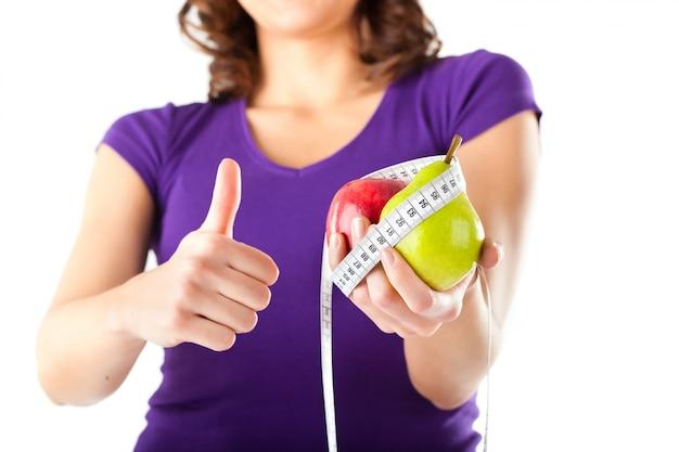 リンゴ、梨、測定テープを持つ女性