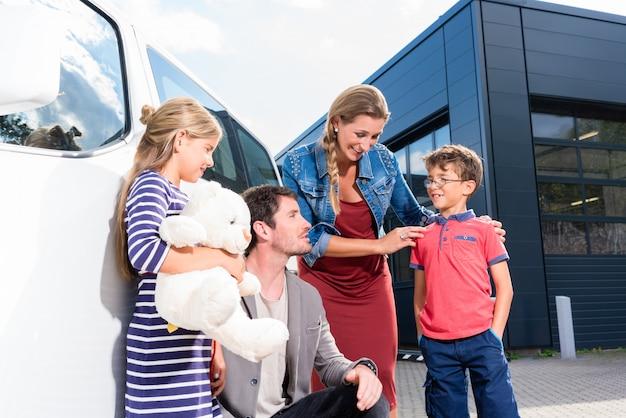 車のディーラーで自動車を買う子供連れの家族