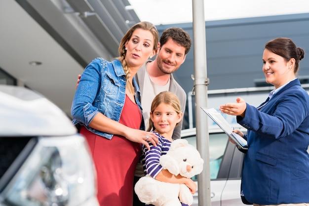 自動車を買うことについて家族に助言する自動車ディーラー