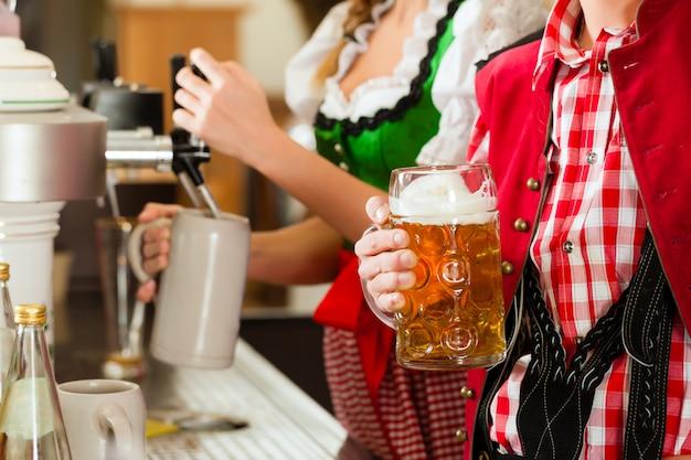 Молодая женщина, рисование пива в ресторане или пабе