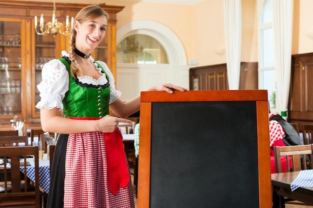 Самка трактирщика в традиционной баварской одежде в пабе