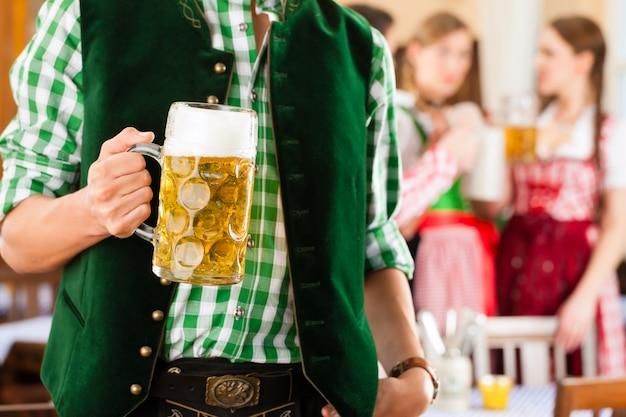 Молодые люди в традиционном баварском трахте в ресторане или пабе