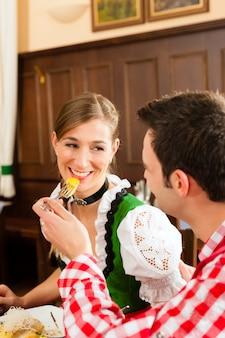 Люди в традиционном баварском трахте едят в ресторане или пабе
