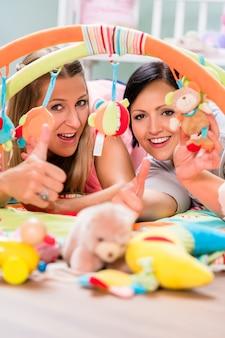乳児用のプレイバーを準備するベビールームを提供する女性