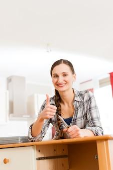 若い女性は食器棚を組み立てています