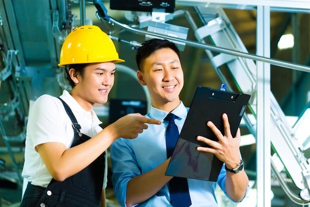 労働者およびクリップボードと生産マネージャー