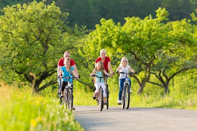 自転車で夏にサイクリングの子供連れの家族