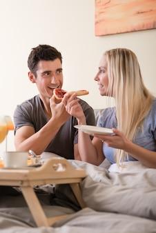 ベッドで朝食を食べて幸せな若いカップル