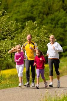 スポーツのための牧草地で実行されている家族