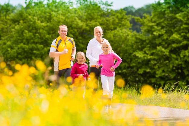 フィットネスのための牧草地でジョギング家族